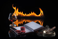 Glass of cognac with poker markers, notebook and cigar Royalty Free Stock Photography