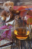 Glass of cognac, red leaves, old book and teddy bear Royalty Free Stock Image