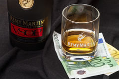 Glass cognac Remy Martin and euro banknotes Stock Images