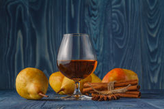 Glass of cognac and ripe juicy pears conference on a dark wooden Stock Image