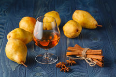 Glass of cognac and ripe juicy pears conference on a dark wooden Royalty Free Stock Images