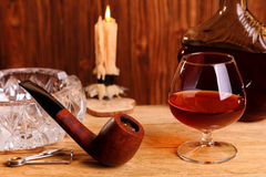 A glass of cognac and smoking pipe Stock Photography