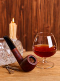 A glass of cognac and smoking pipe Royalty Free Stock Photos