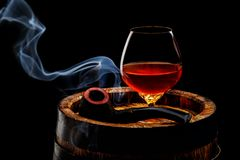 Glass of cognac with smoking pipe on old wooden barrel. In front of black background Royalty Free Stock Photography
