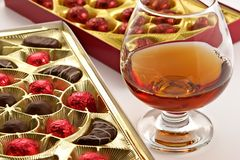 Glass with cognac and sweets with liquor. Isolated on a white background Royalty Free Stock Image