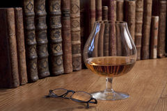 Glass of cognac and vintage books. Glass of cognac standing in front of a row of vintage books Royalty Free Stock Photos