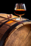 Glass of cognac on the vintage wooden barrel Stock Images