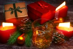Glass with cognac or whiskey, Christmas balls and candles. New Year`s tree, balls and glass with alcohol. royalty free stock photos