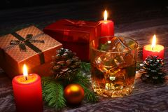 Glass with cognac or whiskey, Christmas balls and candles. New Year`s tree, balls and glass with alcohol. royalty free stock image