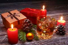 Glass with cognac or whiskey, Christmas balls and candles. New Year`s tree, balls and glass with alcohol. stock images