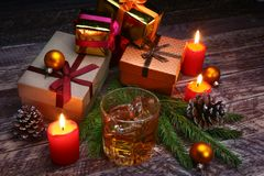 Glass with cognac or whiskey, Christmas balls and candles. New Year`s tree, balls and glass with alcohol. stock photography