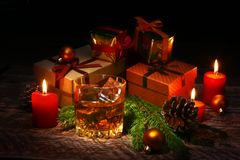 Glass with cognac or whiskey, Christmas balls and candles. New Year`s tree, balls and glass with alcohol. stock photo