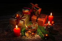 Glass with cognac or whiskey, Christmas balls and candles. New Year`s tree, balls and glass with alcohol. royalty free stock photography