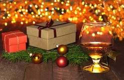 Glass with cognac or whiskey, gift box, colored balls and christmas tree on wooden table. Celebrities composition. Selective focus Stock Images