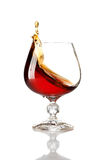 Splash of cognac in glass Stock Images