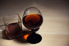 Glass cognac wooden table. Studio quality royalty free stock photos