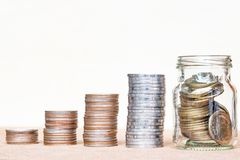 Glass of coin and four pole range of coins on vintage blurred ba royalty free stock photo