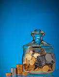 Glass with coins Royalty Free Stock Photos