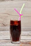 Glass with coke and straw. Ice cube in brown beverage. Dose of refreshment Stock Images