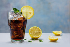 Glass of cola or coke with ice cubes, lemon slice and peppermint Stock Image