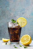 Glass of cola or coke with ice cubes, lemon slices and peppermin Royalty Free Stock Photography
