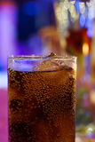 Glass of cola on counter bar at night time Stock Photos