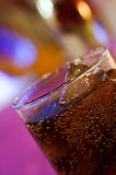 Glass of cola on counter bar at night time Royalty Free Stock Photos
