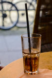 Glass with cola drink and a drinking straw. A close up vertical view of a half full glass of cola with a black drinking straw and in the background two wheels of Royalty Free Stock Image