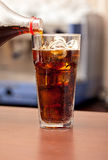 Glass of cola with ice on the bar Stock Photography