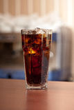 Glass of cola with ice on the bar Royalty Free Stock Photo