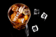 Glass of cola with ice on black table Royalty Free Stock Images