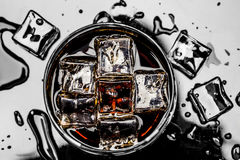 Glass with cola and ice cubes surrounded by ice cubes and water drops Stock Photo