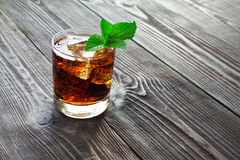 Glass of cola with ice and fresh mint on wooden table. Royalty Free Stock Image