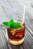 Glass of cola with ice and fresh mint on wooden table. Stock Image