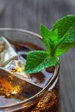 Glass of cola with ice and fresh mint on wooden table. Stock Images