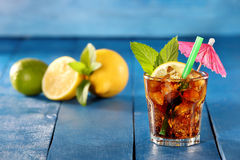 Glass of cola with ice and lemon on blue background Stock Photo