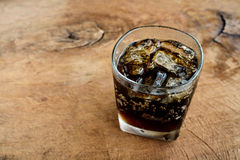 A glass of cola with ice on old wood Royalty Free Stock Photos