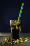 Glass of cola with ice. On old wooden table stock photo