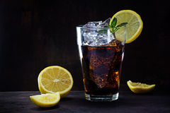 Glass of cola or ice tea with lemon slices and peppermint garnis Stock Photography