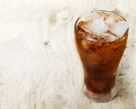 Glass of cola. With ice on wooden plank royalty free stock photos