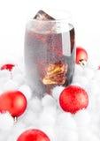 Glass of cola soda  on snow and christmas balls Royalty Free Stock Photography