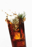 Glass of Cola and Southernwood splashing, close-up. Against white background Stock Photo