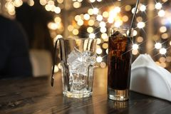 Glass of cold alcohol drink with ice on table Stock Photography