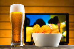 Glass of cold beer and chips. Football match in background Royalty Free Stock Photos