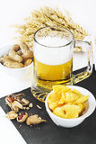 Glass of cold beer with chips and peanuts isolated on white back Stock Image