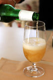 Glass of cold beer filling from the bottle Royalty Free Stock Photo