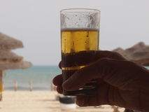 Glass of cold beer. The glass of cold beer is held in hand by the tourist sunbathing on the beach stock photo