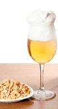 Glass of cold beer and nuts over wooden surface Stock Images