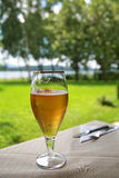 Glass of cold beer on table. Glass of cold beer on white tablecloth and cutlery royalty free stock photo
