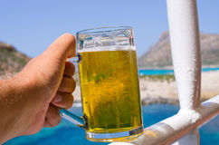 Glass of cold beer in tropics Stock Photo